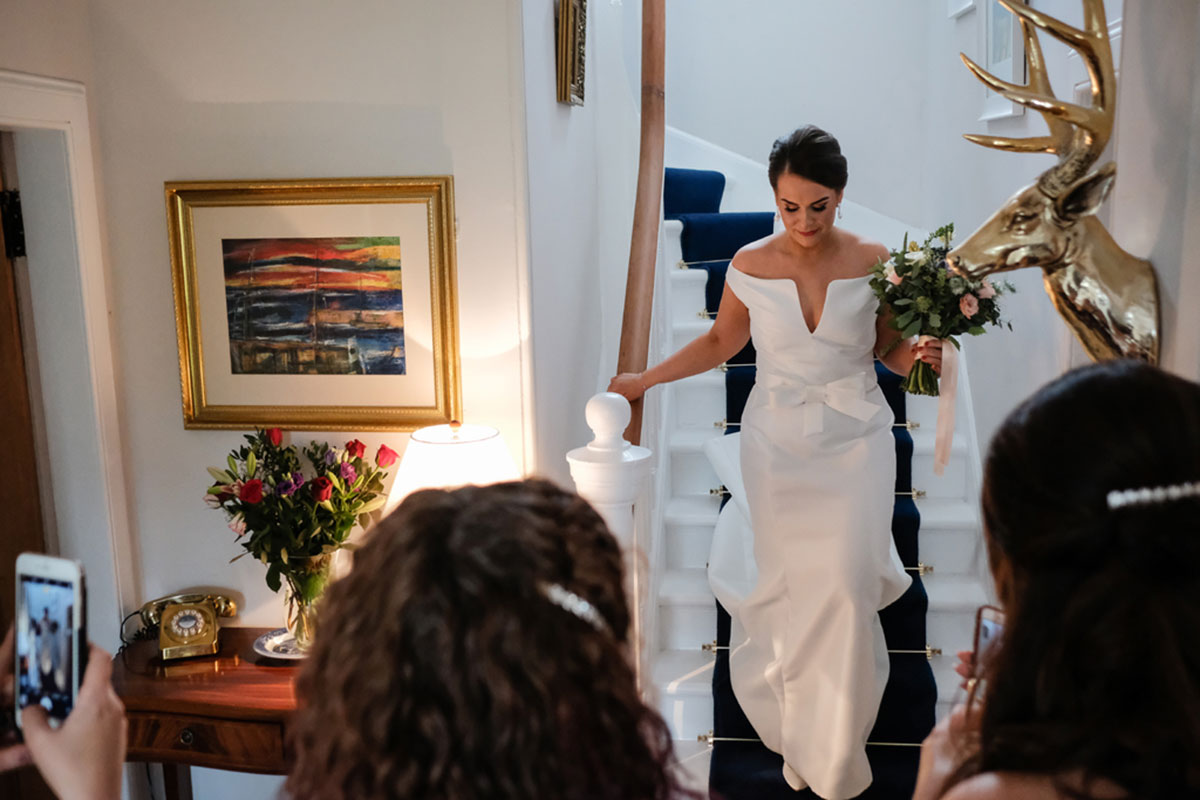 bride-coming-down-stairs-bridesmaids-taking-photo