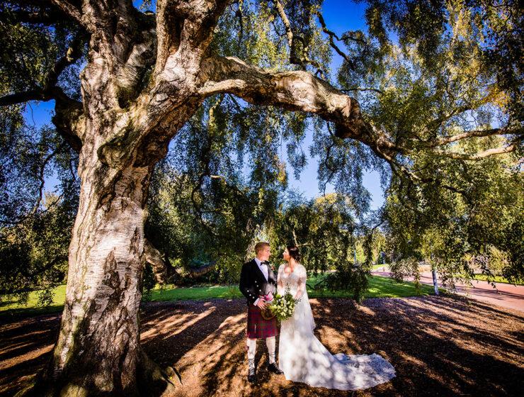 _bride-and-groom-standing-under-tree