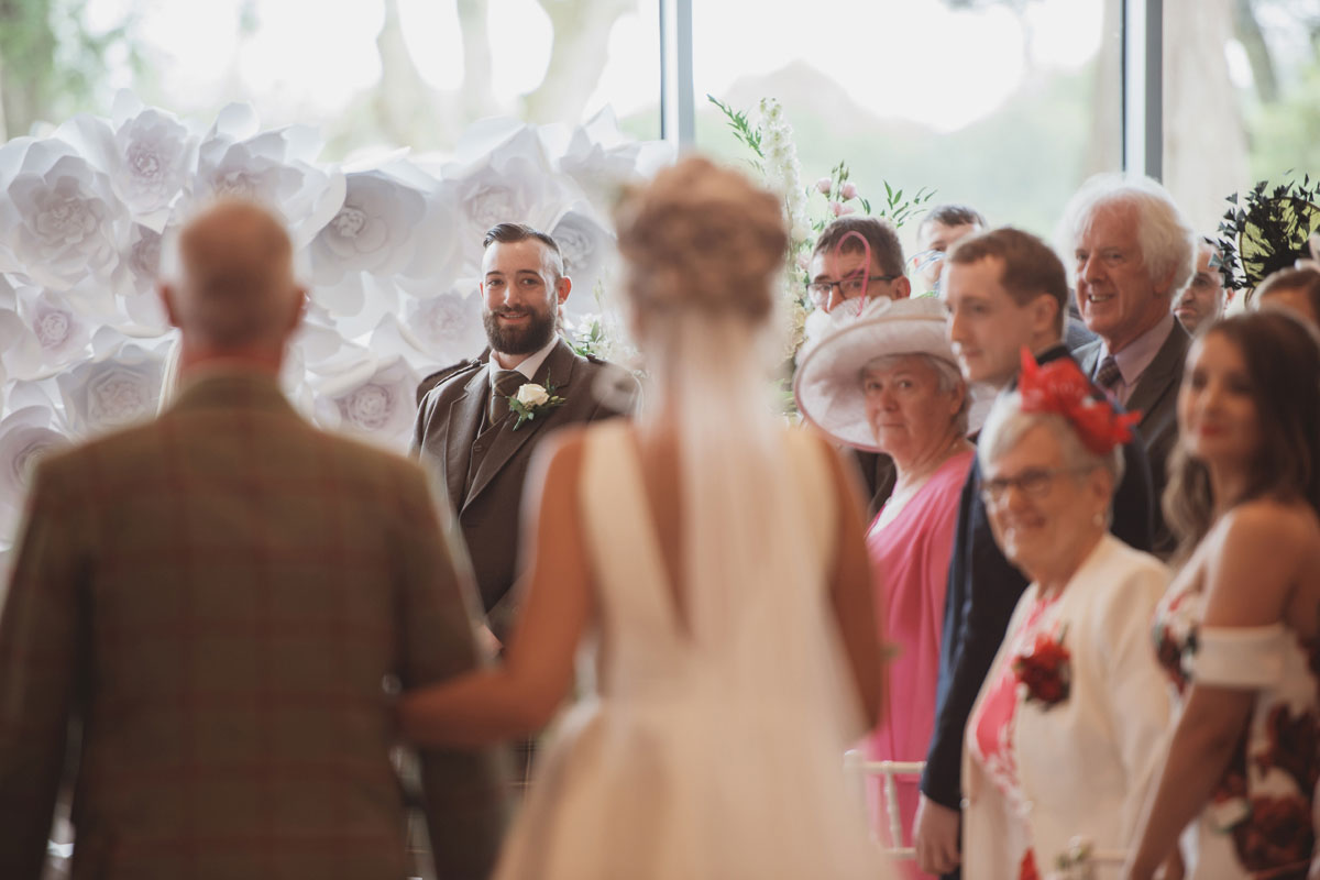 Aboyne Photographics Meldrum House Aberdeen wedding venue bride walking down aisle with dad and groom watching