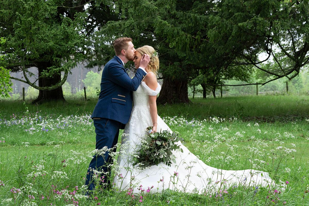groom-kissing-bride-head-errol-park