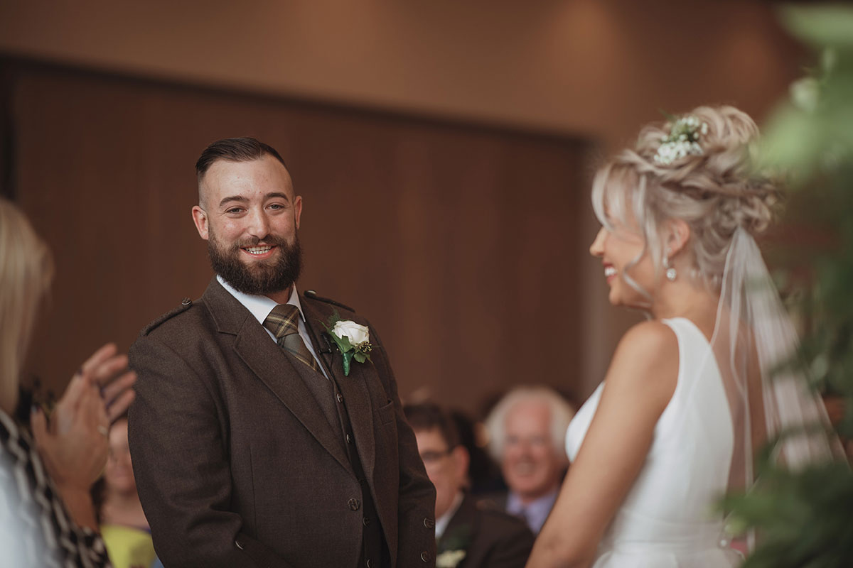 Aboyne Photographics Meldrum House Aberdeen wedding venue groom laughing with bride during ceremony