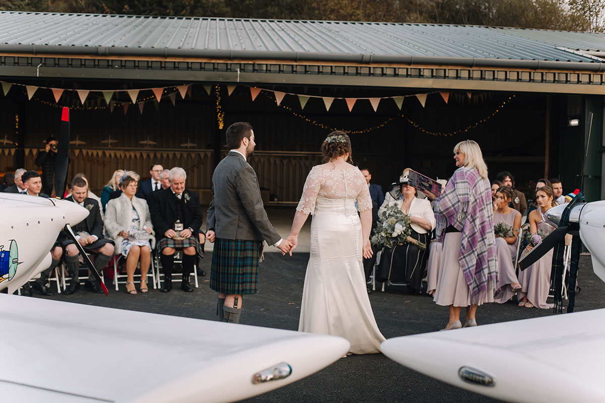 wedding-ceremony-on-runway-oban-airport-rear-view-of-couple