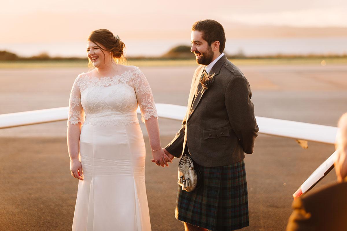 bride-groom-holding-hands-oban-airport-sunset