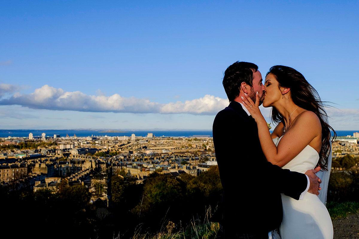 bride-groom-kissing-calton-hill-view-of-edinburgh