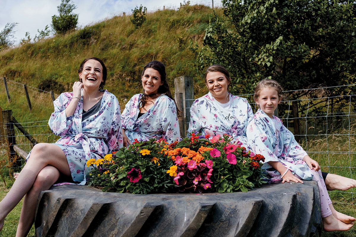 Isle-of-Lismore-Wedding-Photography-Barry-Robb-bridesmaids-sitting-on-tractor-wheel-filled-with-flowers