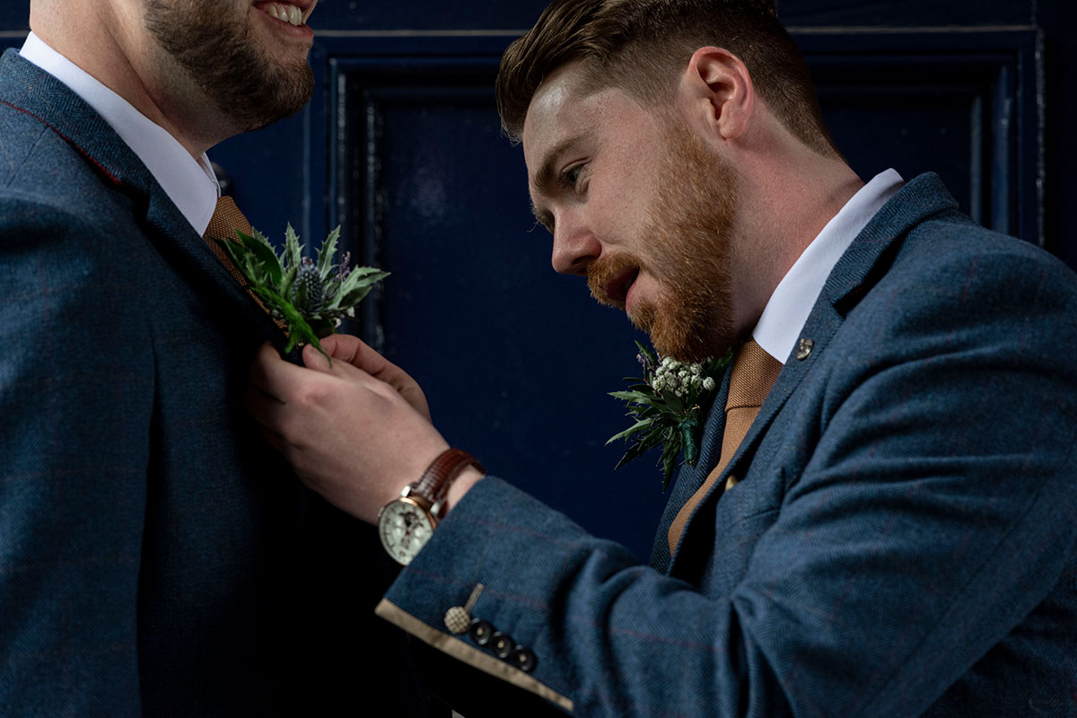 groom-blue-suit-pinning-buttonhole