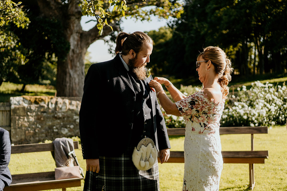 lady-fixing-grooms-buttonhole-fife-wedding-victoria-photography