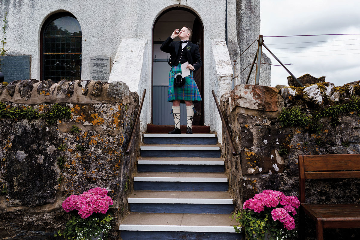 Isle-of-Lismore-Wedding-Photography-Barry-Robb-usher-outside-church-drinking-from-hipflask