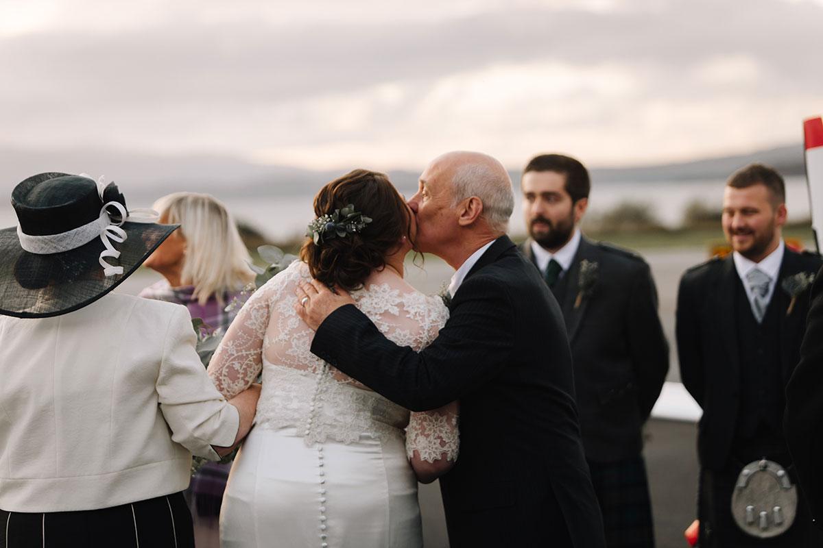 dad-kissing-bride-on-head-at-oban-airport-wedding