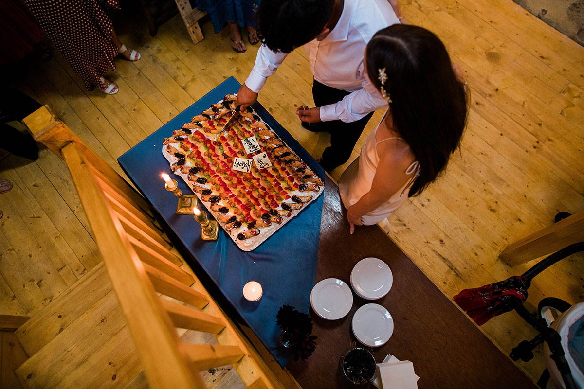 cormiston farm wedding mirrorbox photography bride and groom cutting into cannoli