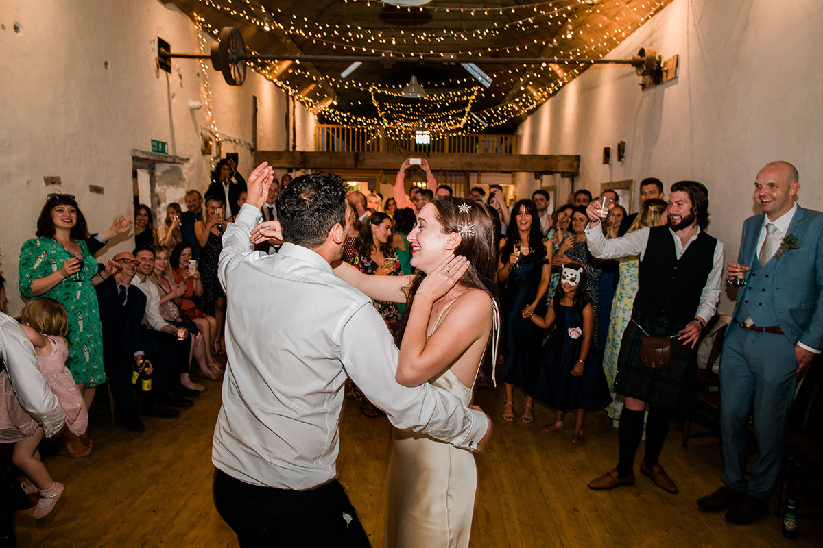 cormiston farm wedding mirrorbox photography bride and groom dancing with guests looking on