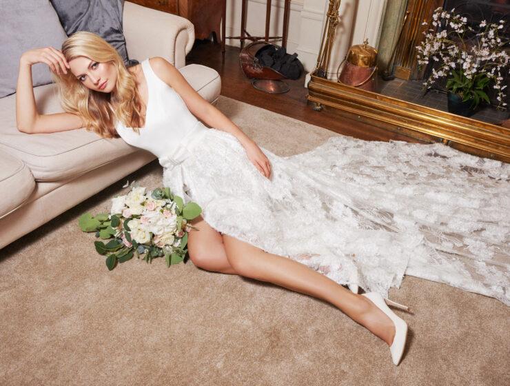 bride leaning on sofa wearing Joyce Young wedding dress