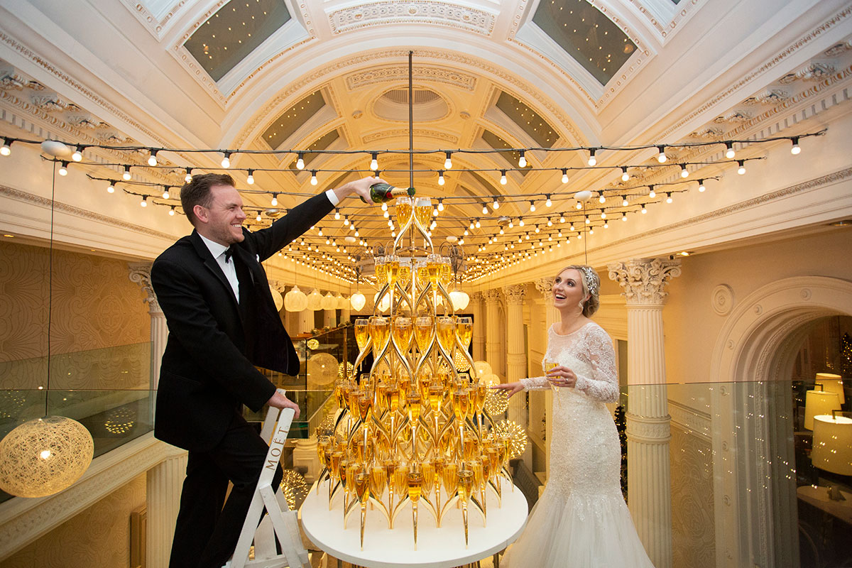 bride and groom pouring over a champagne tower at the corinthian in glasgow