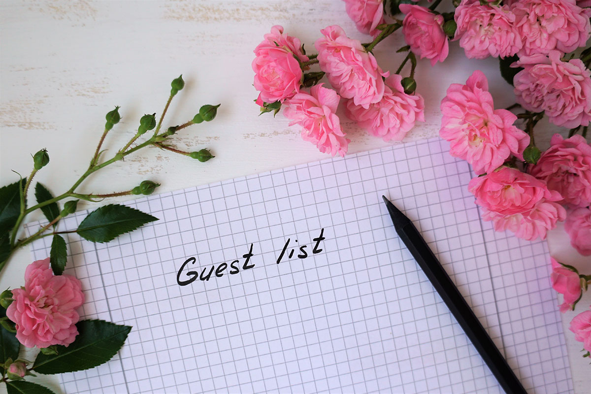 wedding-guest list notes on squared paper, a pen and pink flowers