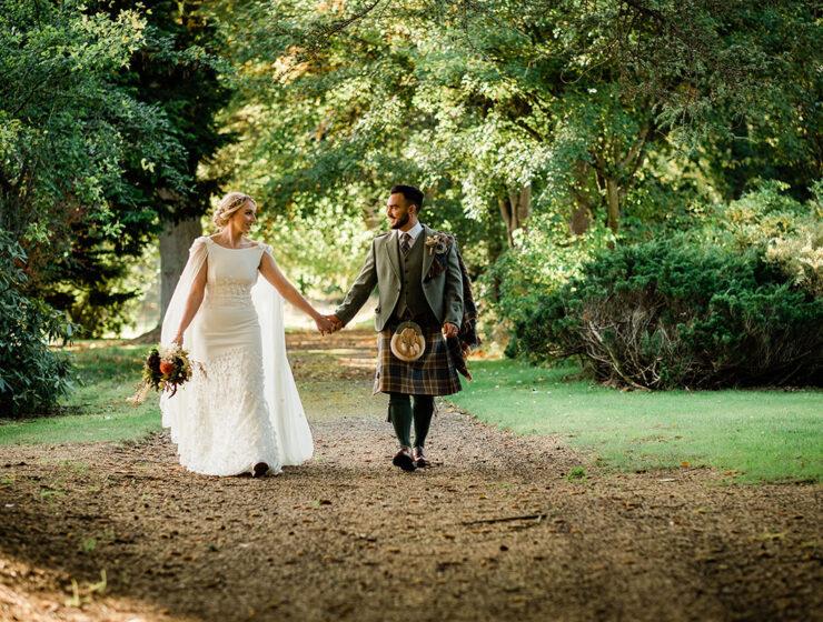 Bride and groom walking in grounds at Errol Park