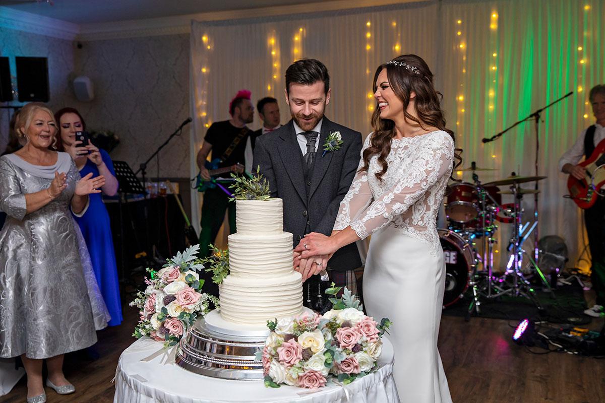 newlyweds cutting cake festive wedding Inglewood House