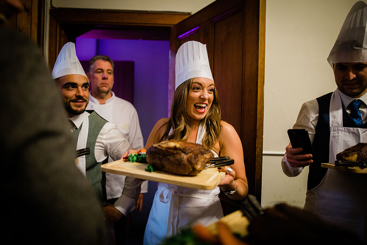 guest wearing chefs hat and carrying board with roasted meat