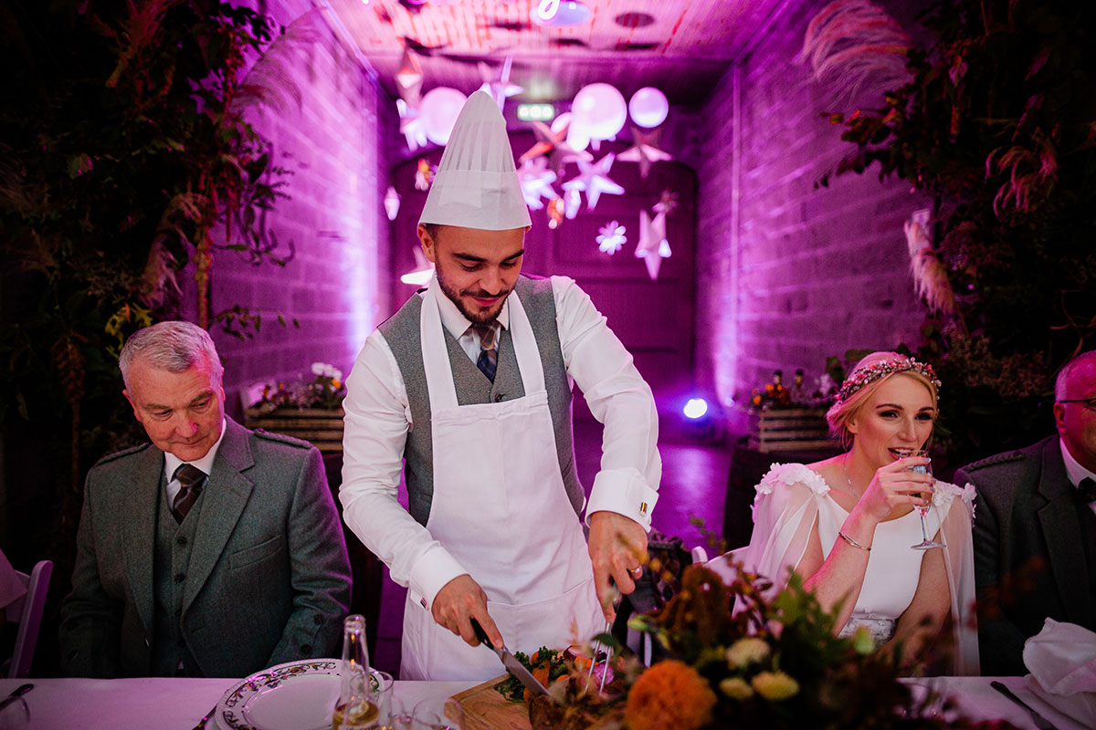 groom wearing chefs hat and carving meat at top table