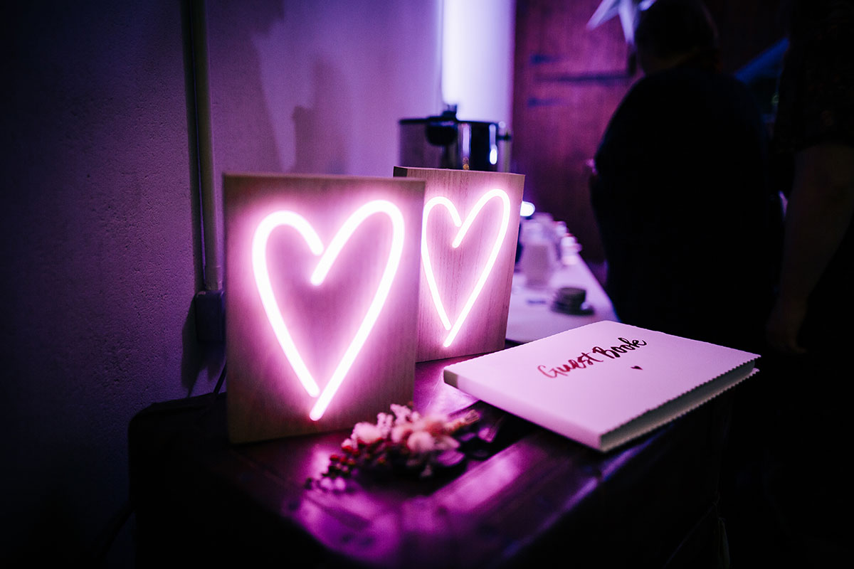 guest book and neon love heart signs at wedding
