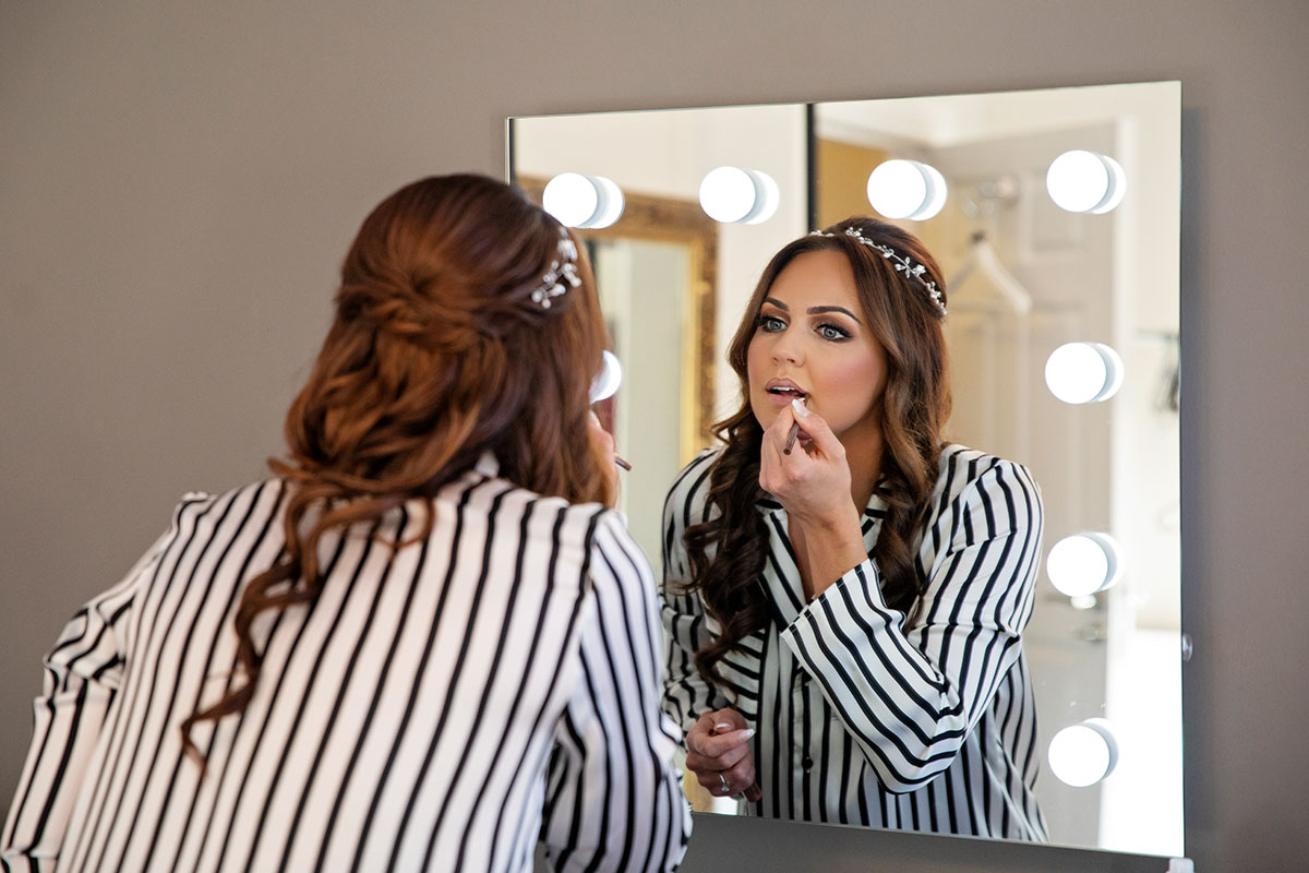 bride in striped pyjamas doing makeup in mirror