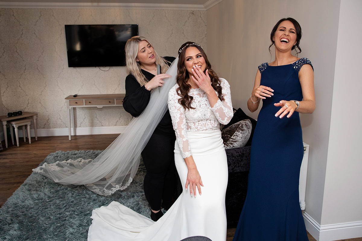 bride giggling with bridesmaid and hairstylist applying veil
