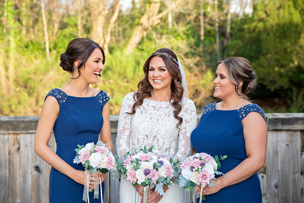 bride smiling with two bridesmaids wearing blue