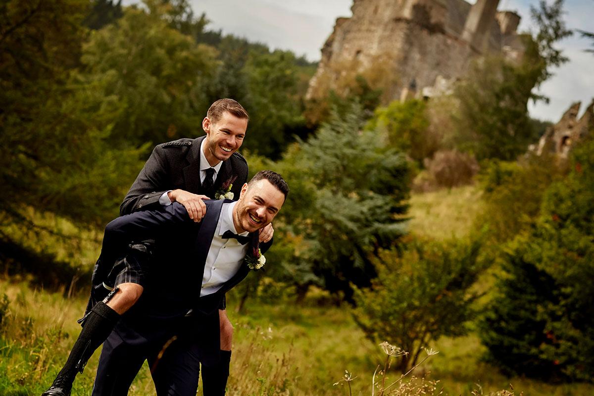 groom giving groom piggy back at Neidpath Castle