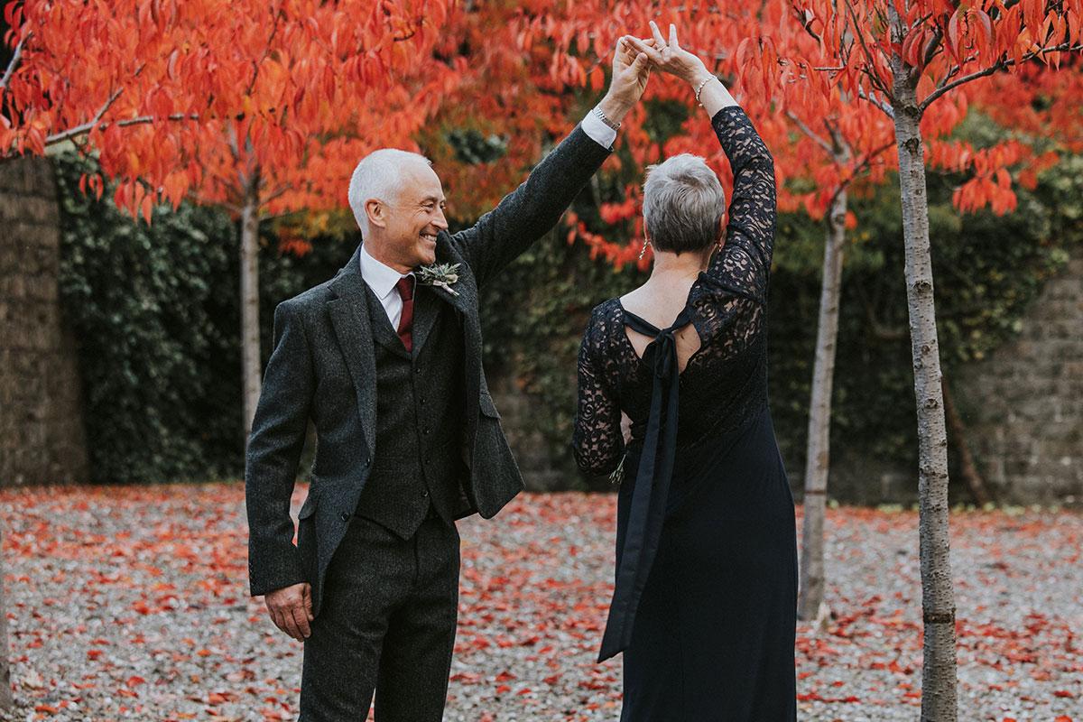 Older couple dancing beside autumn trees Norton House Hotel