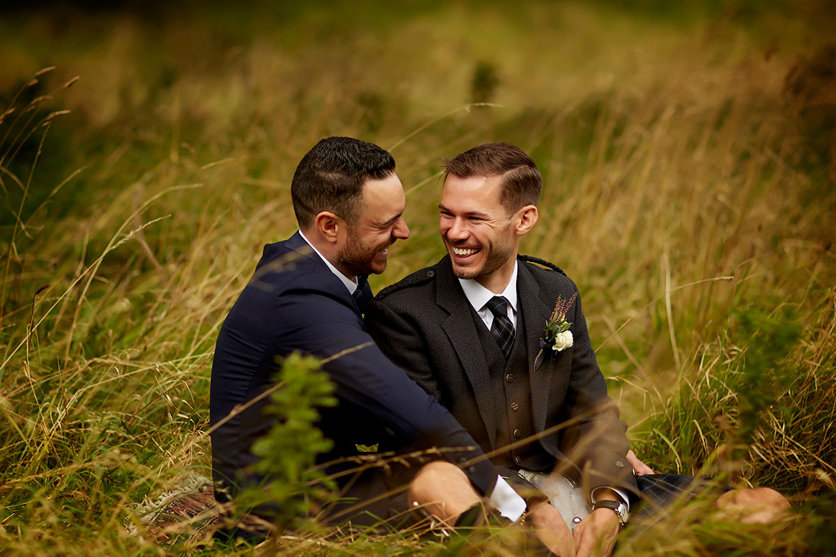 Story of Love Photography two grooms outside Neidpath Castle sitting in grass