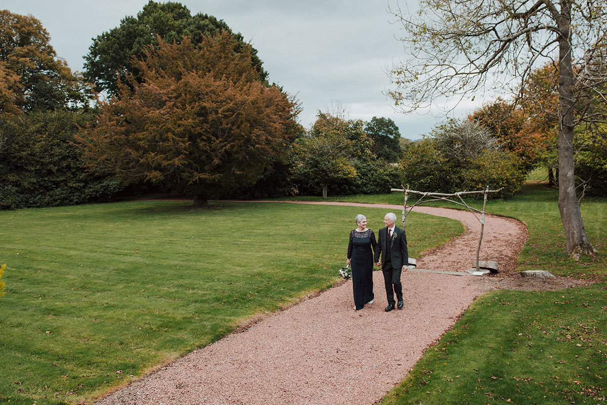 Older bride and groom walking in grounds Norton House Hotel Iris Art Photography