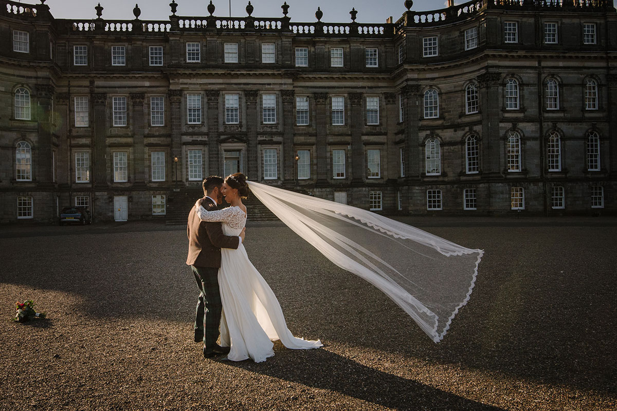 groom and bride with veil flowing in breeze outside Hopetoun House