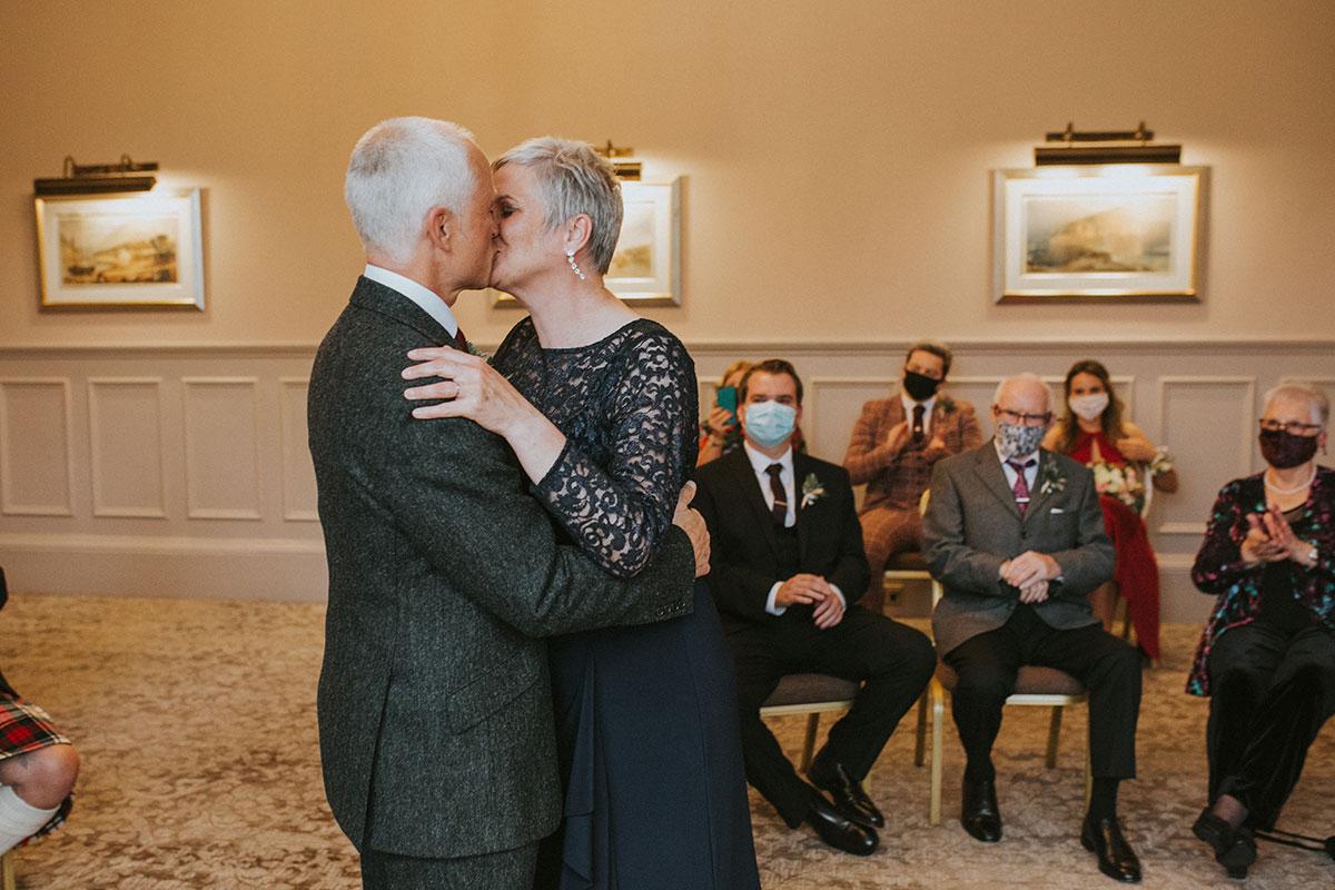 Older couple wedding ceremony kiss Iris Art Photography