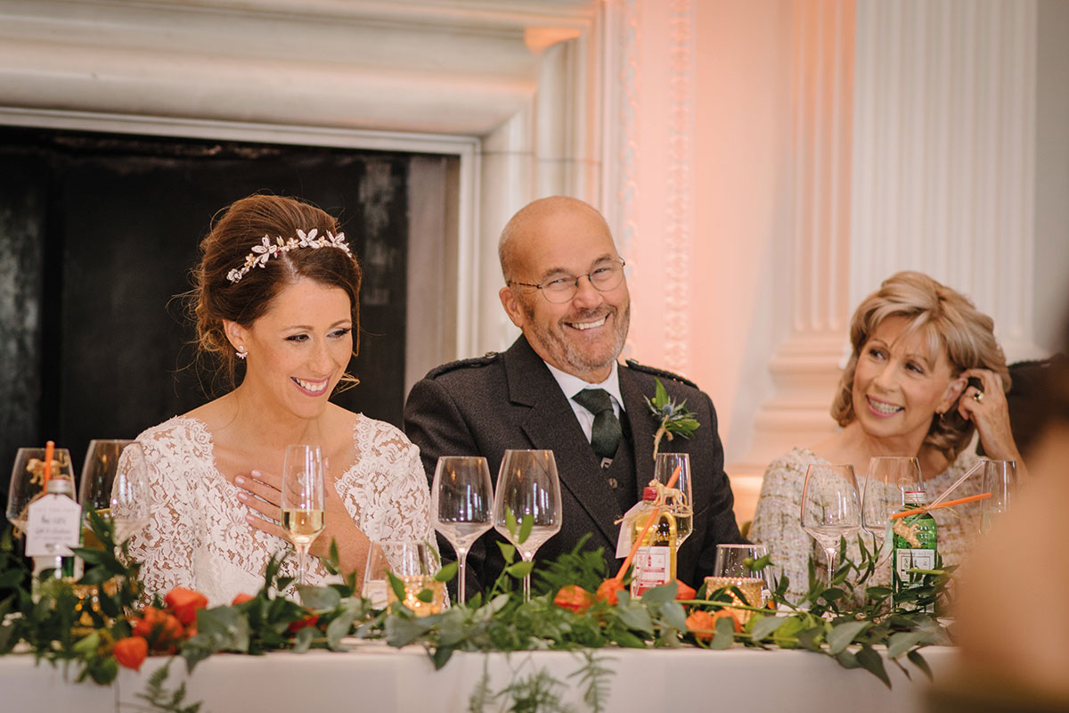 bride, dad and mum laughing at wedding speeches