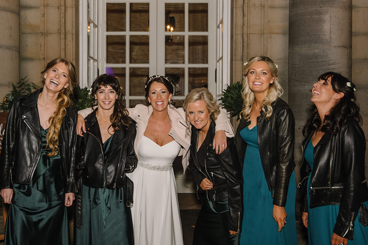 bride with 4 bridesmaids wearing leather jackets