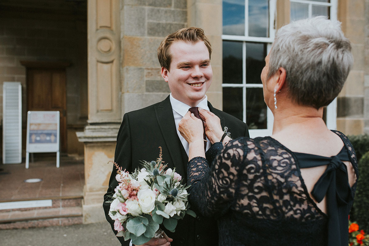 woman fixing man's tie at a wedding