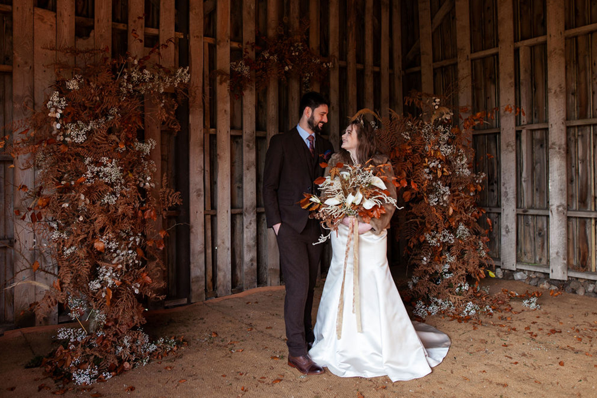 bride and groom under an autumnal wedding arch
