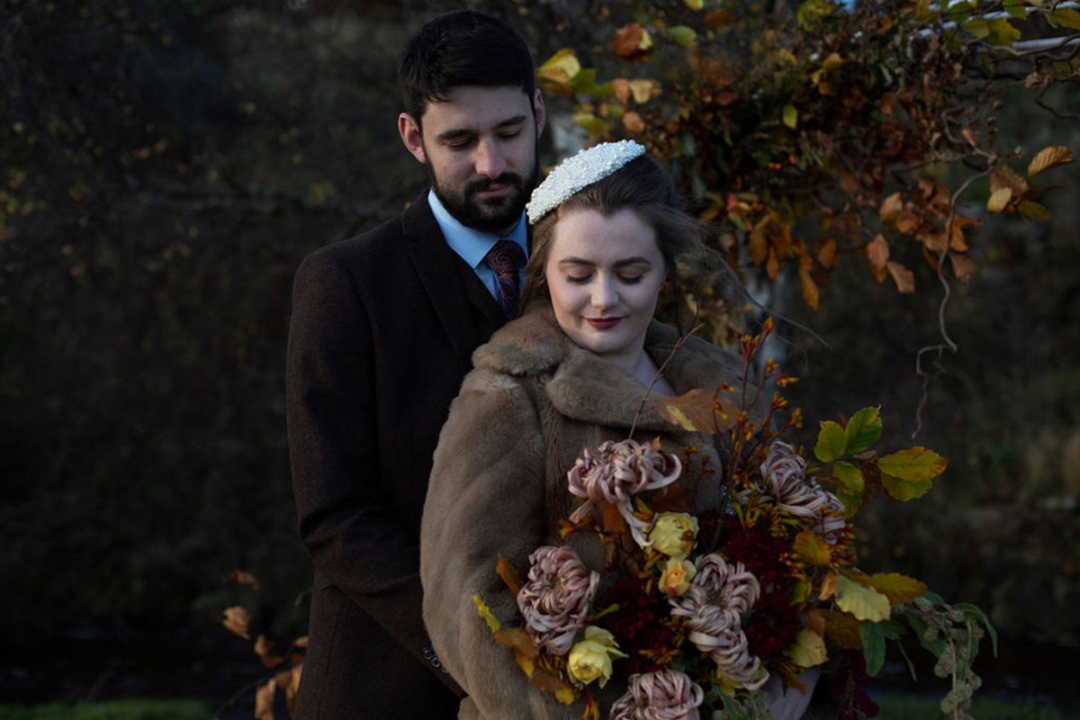 bride and groom with autumnal bouquet and percher hat