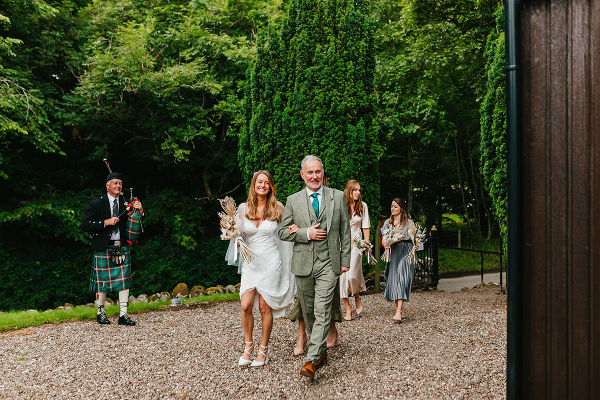 bride, dad and wedding party being piped to wedding ceremony