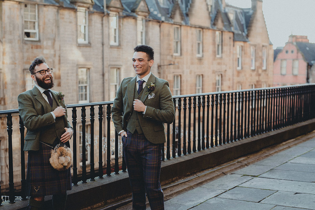 Two laughing grooms in Edinburgh's Old Town wearing outfits from Gordon Nicolson Kiltmakers