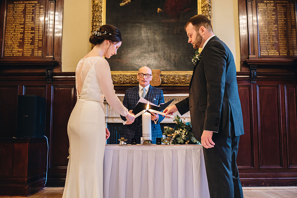 bride and groom lighting candles during wedding ceremony at Trades Hall Glasgow elopement