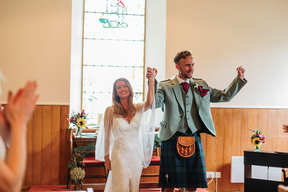just married bride and groom raising hands at Clova Kirk