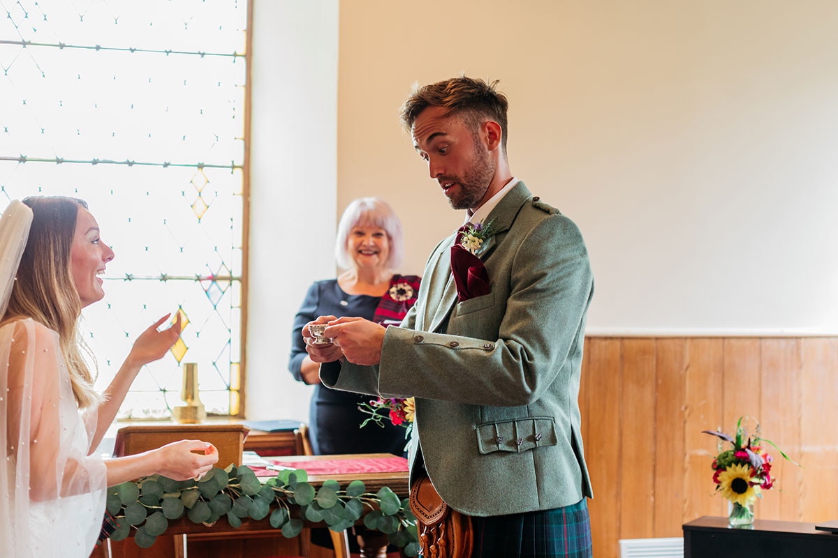 groom drinking whisky from quaich while bride and celebrant watch on