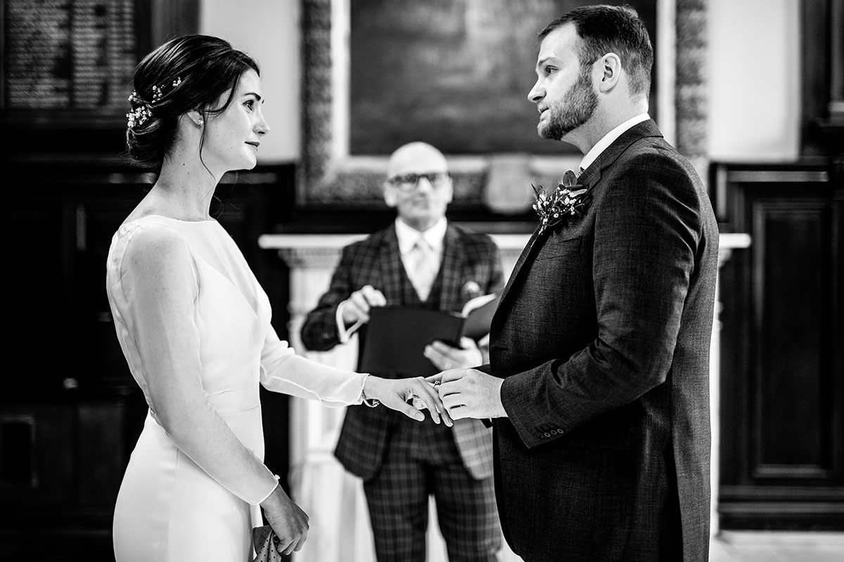 bride and groom exchange rings during wedding ceremony Trades Hall Glasgow elopement