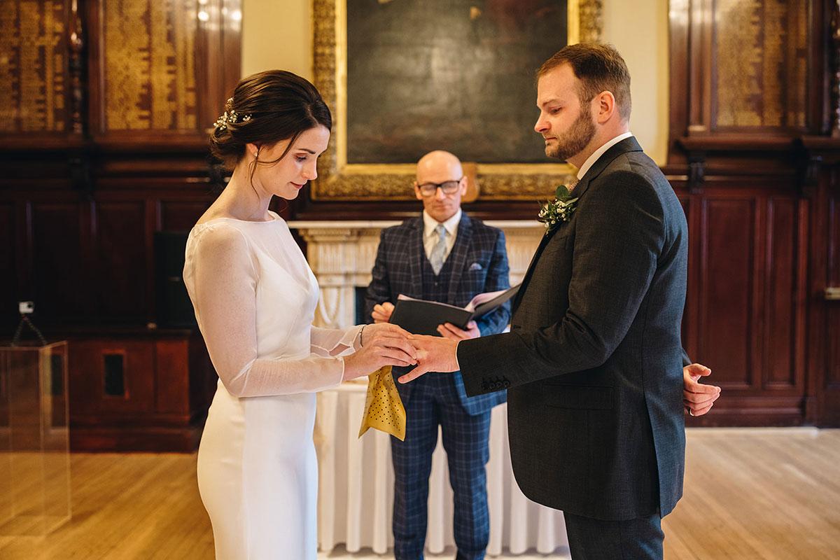bride puts wedding ring on groom during wedding ceremony Trades Hall Glasgow elopement