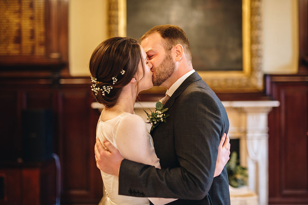 bride and groom kiss and newlyweds during wedding ceremony at Trades Hall Glasgow elopement
