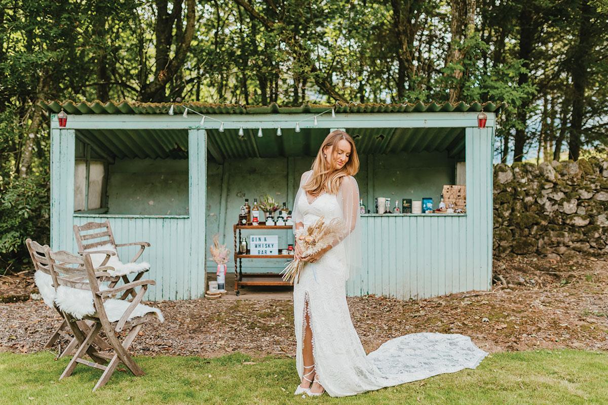 bride posing outside DIY gin bar at Glen Clova