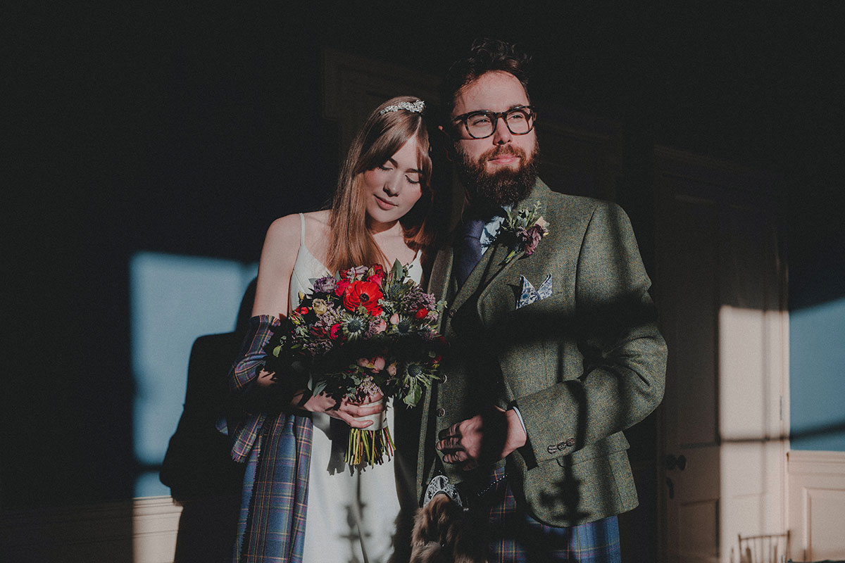 Bride wearing a dress from Kudos Bridal Boutique and groom wearing kilt outfit by Gordon Nicolson Kiltmakers at Riddle's Court in Edinburgh