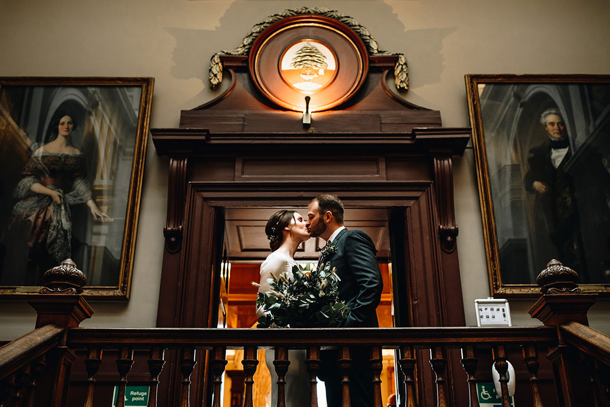 bride and groom kiss after wedding ceremony at Trades Hall Glasgow elopement