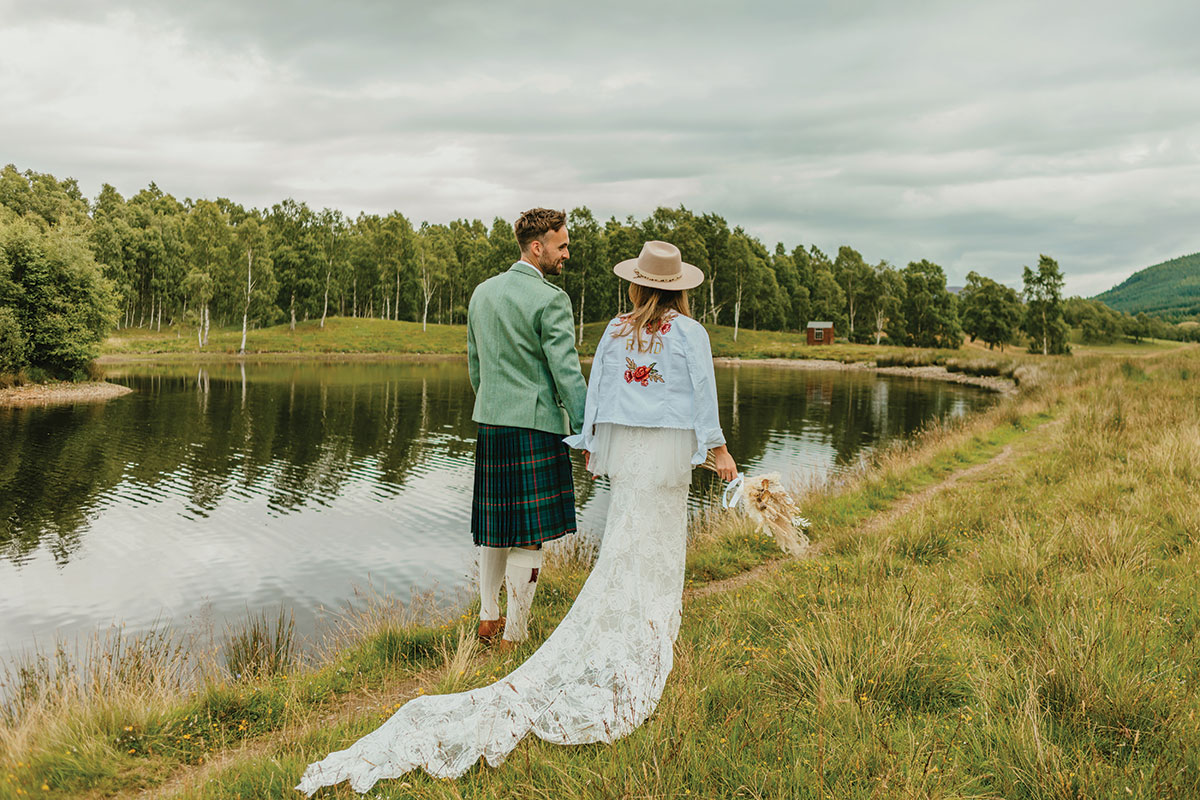 bride and groom walking next to loch at Glen Clova
