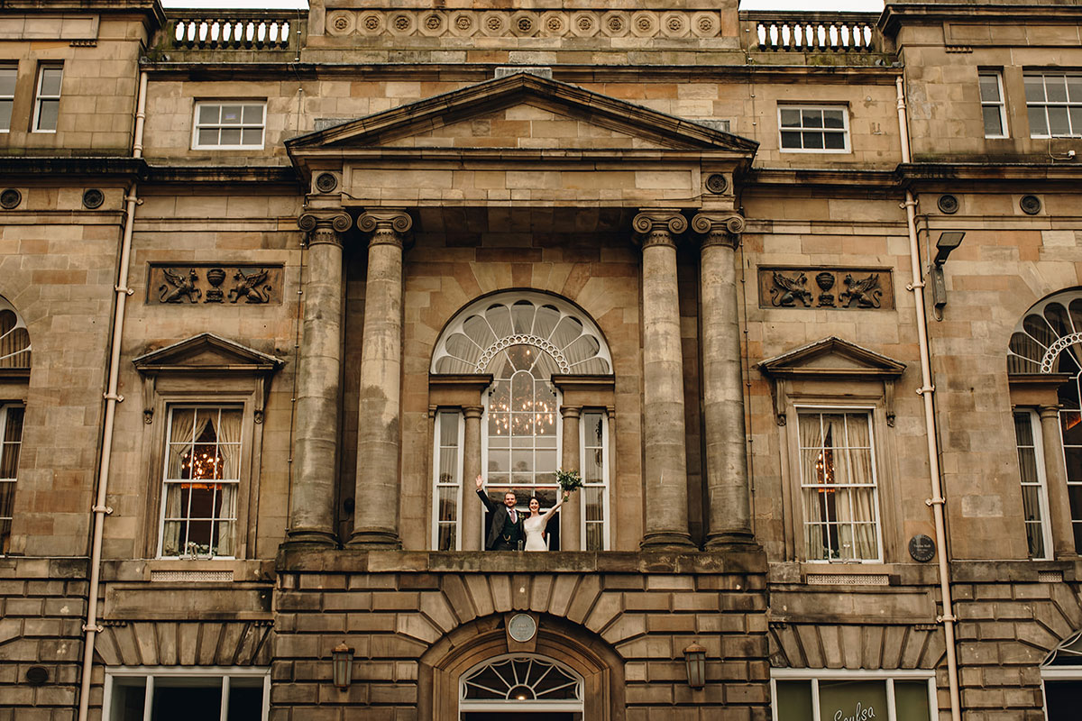 bride and groom wave from exterior balcony of Trades Hall Glasgow